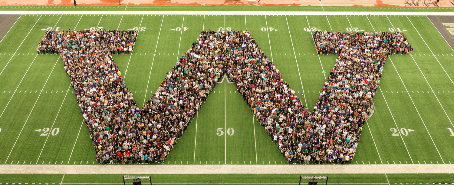 """Photo of UW students in the shape of a """"W"""" on the Husky Stadium field."""