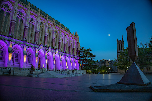 Suzzallo Library at the University of Washington Seattle campus at night is lit by purple floodlights, with a sculpture in the foreground and the moon beyond.